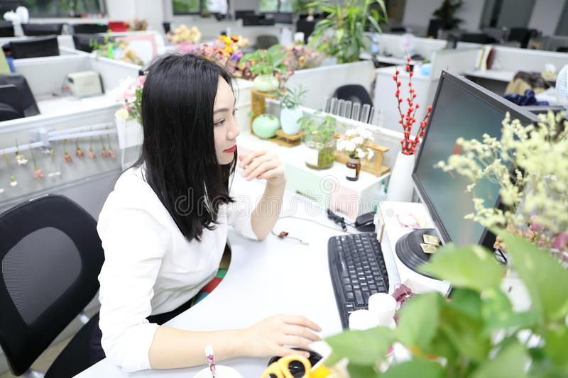 Asia Chinese office lady woman girl sit on chair thinking at work laptop computer smile wear business occupation suit workplace. There is a young pretty stock photography