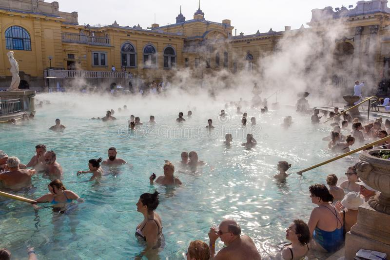 Thermal baths Széchenyi in open air with relaxing people on sunny day. Famous hungarian spa baths. royalty free stock image