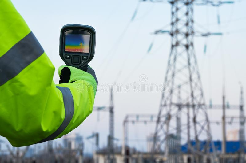Thermal imaging inspection of electrical energy equipment. Electrician use thermal imaging camera for temperature inspection of outdoor electricity substantion stock image