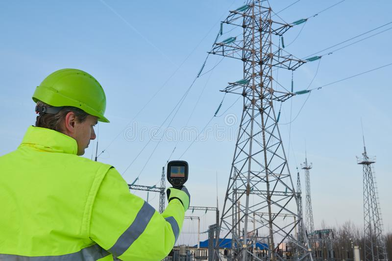 Thermal imaging inspection of electrical energy equipment. Electrician use thermal imaging camera for temperature inspection of outdoor electricity substantion royalty free stock photography