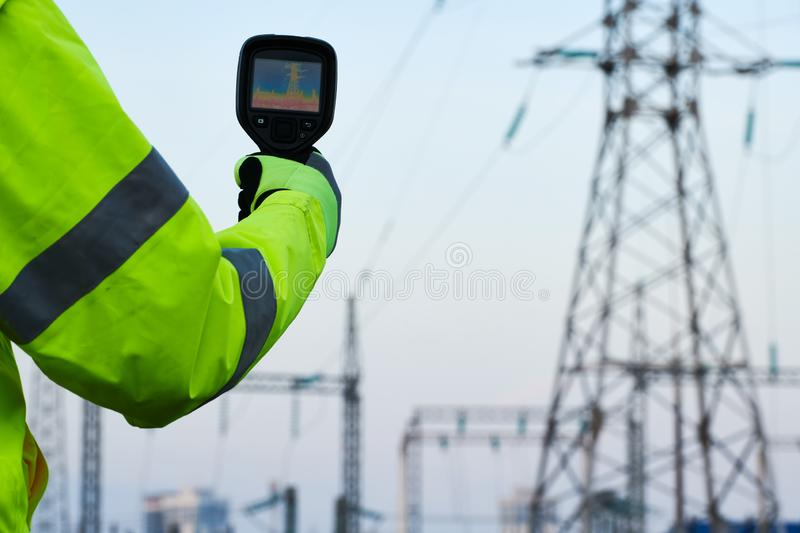 Thermal imaging inspection of electrical energy equipment. Electrician use thermal imaging camera for temperature inspection of outdoor electricity substantion royalty free stock image