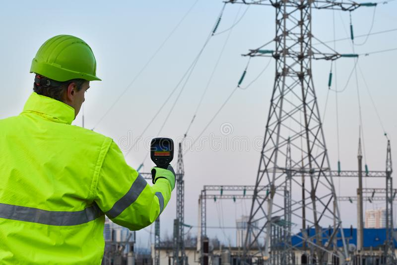 Thermal imaging inspection of electrical energy equipment. Electrician use thermal imaging camera for temperature inspection of outdoor electricity substantion royalty free stock photos