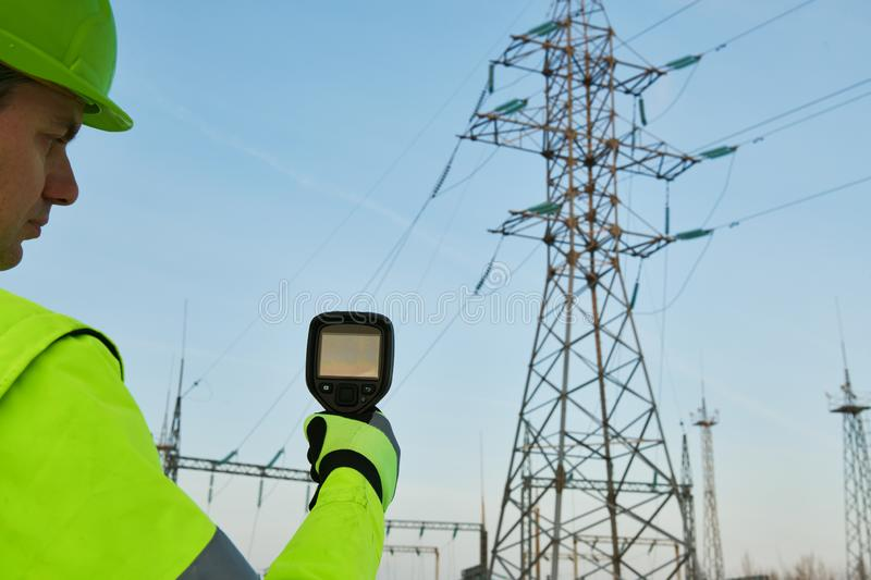 Thermal imaging inspection of electrical energy equipment. Electrician use thermal imaging camera for temperature inspection of outdoor electricity substantion royalty free stock images