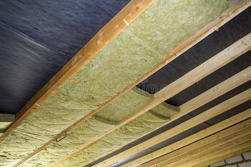 Thermal insulation mineral rock wool installation at the new building attic ceiling royalty free stock images