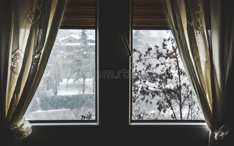 Thermal insulation window save energy bills snow fall view winter dark window curtain stay home snowing outside stock photos