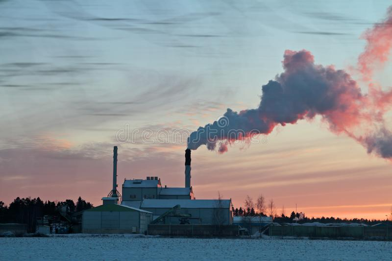 A thermal power factory in the evening light. A thermal power factory steaming in the winter evening at sun set stock photo