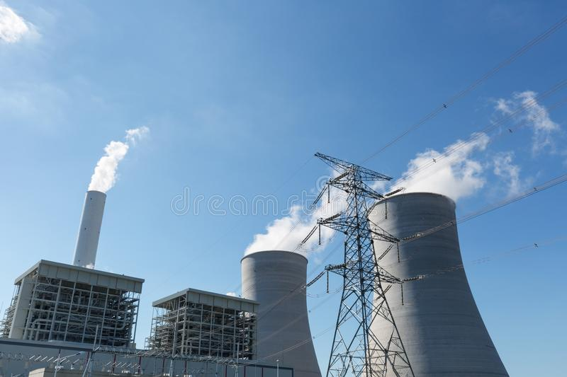 Thermal power plant and electricity pylon. Modern thermal power plant and high voltage transmission pylon against a blue sky stock photography