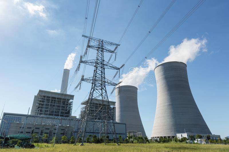 Thermal power plant and electricity pylon. Thermal power plant and high voltage transmission pylon against a blue sky stock image