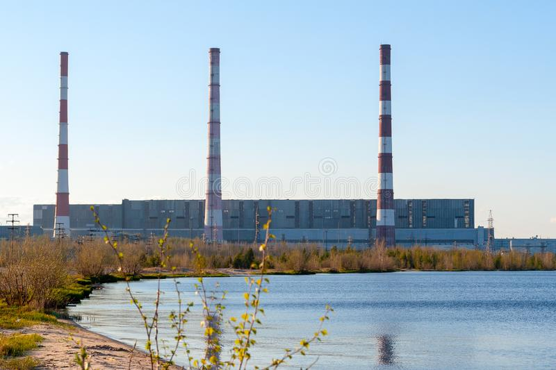 Thermal power station on the shore of the reservoir in the spring evening royalty free stock photography