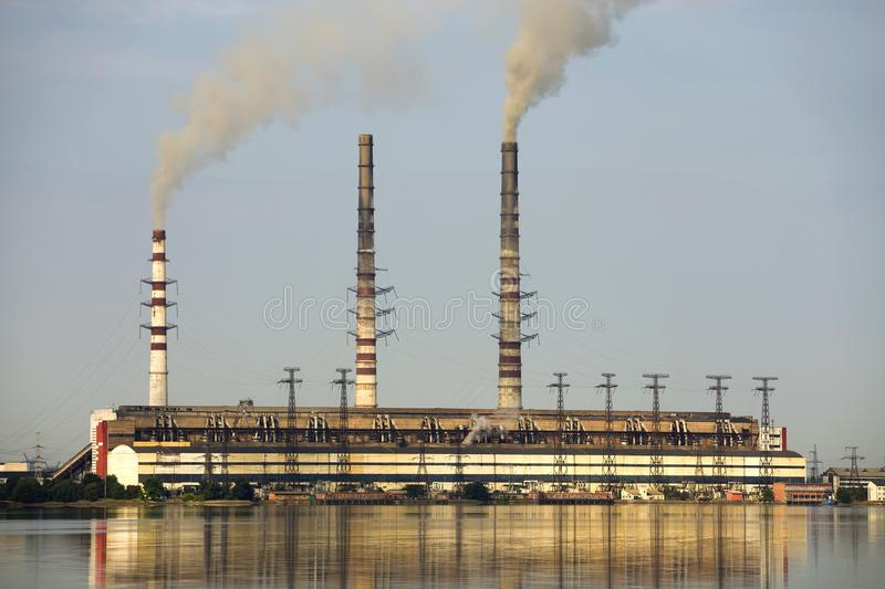Thermal power station tall pipes with thick smoke reflected in lke water surface. Pollution of environment concept stock photography