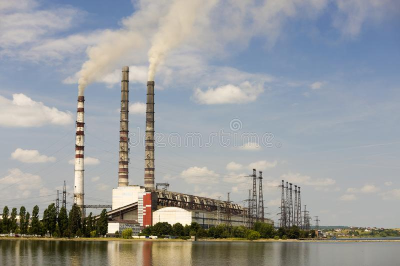 Thermal power station tall pipes with thick smoke reflected in lke water surface. Pollution of environment concept stock images
