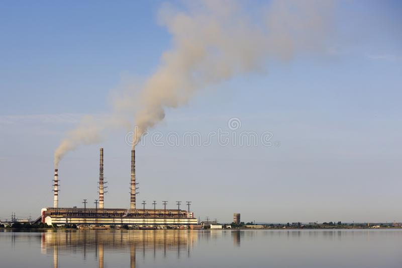 Thermal power station tall pipes with thick smoke reflected in lke water surface. Pollution of environment concept royalty free stock photos
