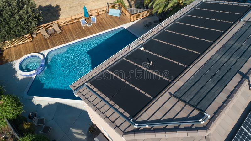 Thermal Solar Panels Installed on the Roof of a Large House. Thermal Solar Panels Installed on the Roof of a Large New House with a Pool stock image