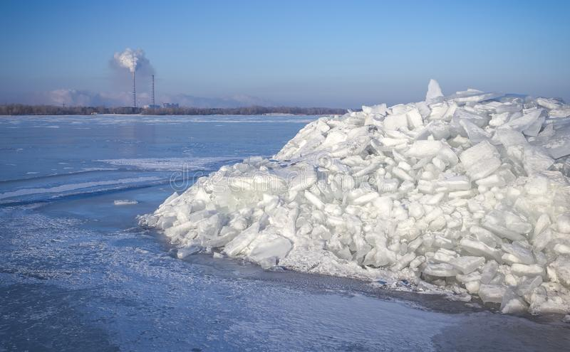 Thermal station and a pile of ice on a frozen river stock photography