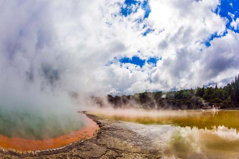 Thermal Wonderland of hot waters. Picturesque lake of multicolored thermal waters evaporates in the air. Thermal Wonderland of hot waters is Wai - O - Tapu. New stock photos