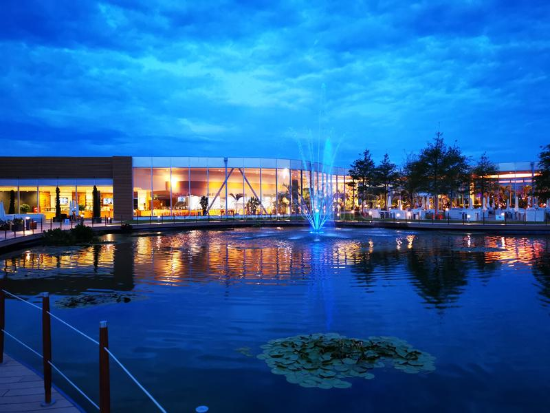 Therme Bucharest outdoor in the night. Lake with decorative fountains colorful near the restaurant area royalty free stock images