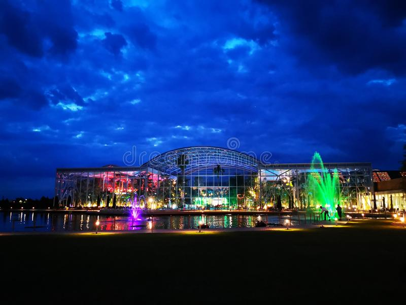 Therme Bucharest outdoor in the night. Lake with decorative fountains colorful in front of the outdoor swimming pools stock photos