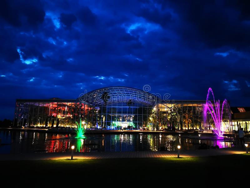 Therme Bucharest outdoor in the night. Lake with decorative fountains colorful in front of the outdoor swimming pools royalty free stock photography