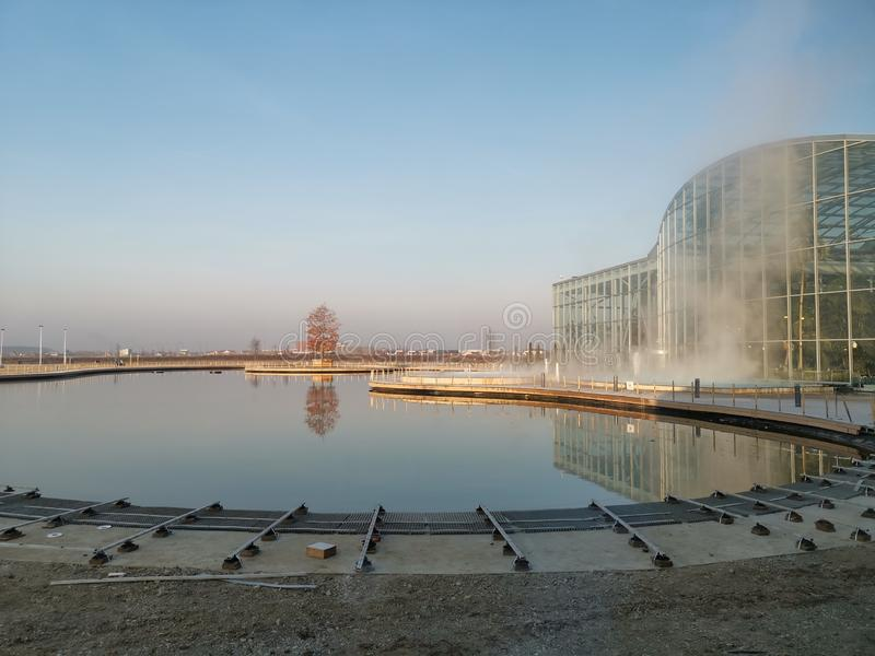 Therme Bucharest outdoor - thermal pool. Therme Bucharest outdoor - steam above thermal pool and facade overlooking the lake royalty free stock images