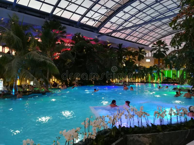 Therme Bucharest, Palm Zone in the night. Indoor pool with thermal water and colorful lights royalty free stock photography
