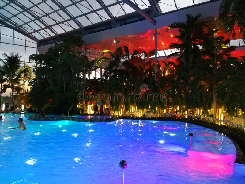 Therme Bucharest, Palm Zone in the night. Indoor pool with thermal water and colorful lights royalty free stock image