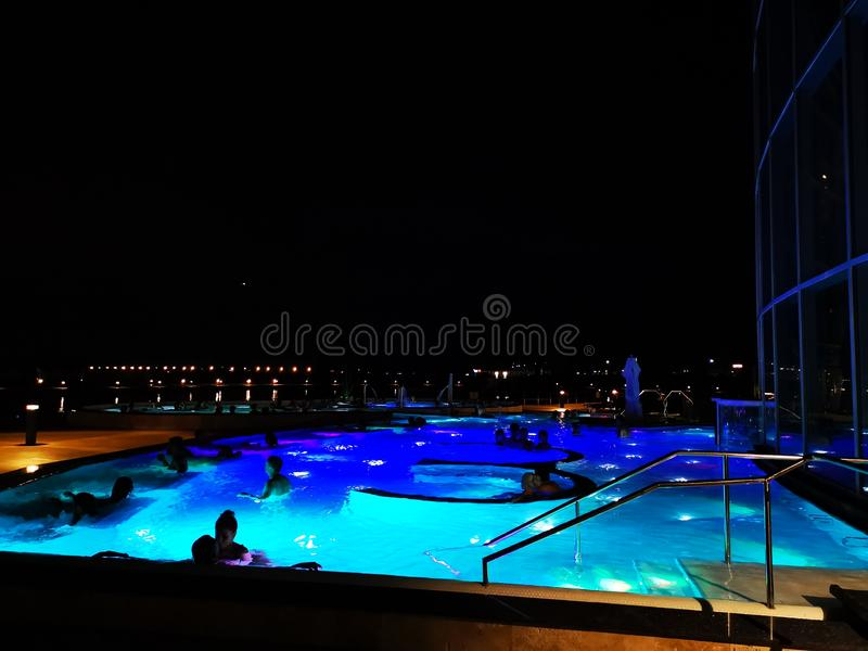 Therme Bucharest, Palm Zone outdoor in the night. Therme Bucharest, Romania, Palm Zone outdoor in the night - people in the pool with thermal water and colorful stock photo