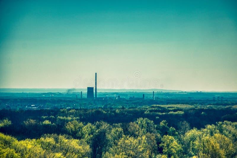 Thermische elektrische centraleschoorstenen tussen bosbomen stock fotografie