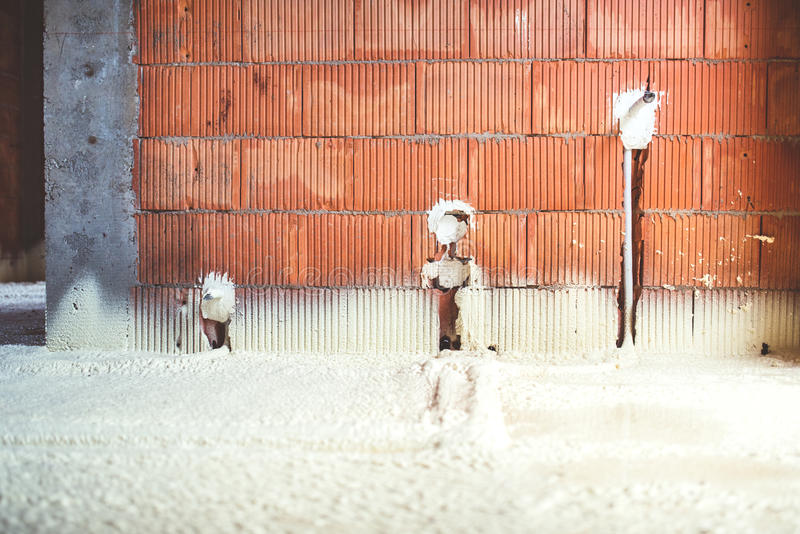 Thermo insulation with spray foam, brick walls and electricity lines at construction site. Thermal insulation with spray foam, brick walls, electricity lines at stock image