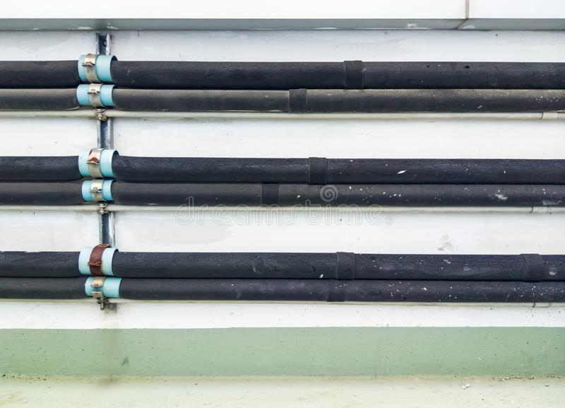 Thermo pipeline with the black rubber case. Thermo pipeline with the black rubber case of the air compressor unit on the terrace of office building stock image