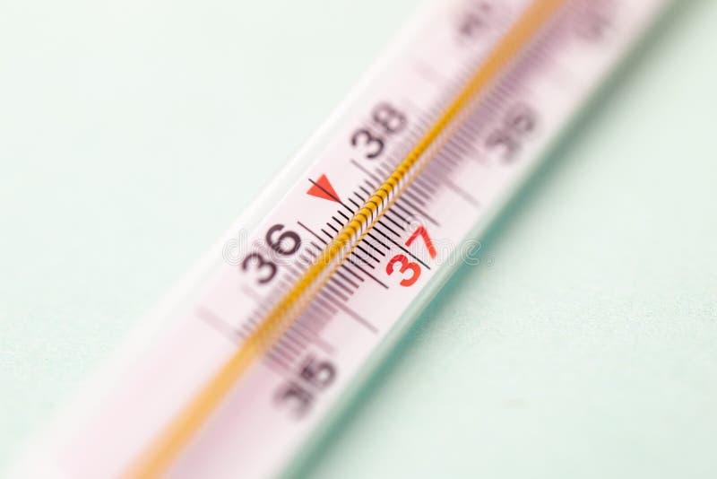 Thermomètre à mercure d'isolement sur le fond blanc, foyer sur 37 degrés image stock