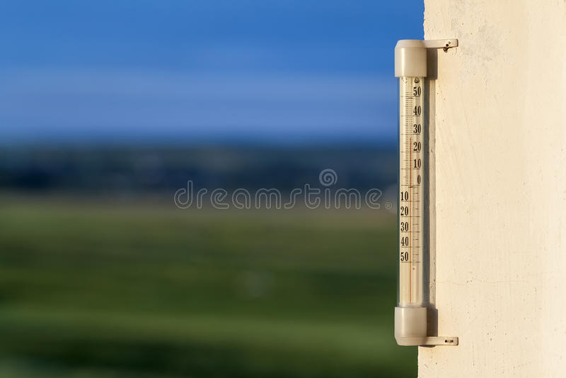Thermomètre Celsius montrant la température chaude sur le Ba vert brouillé photographie stock libre de droits