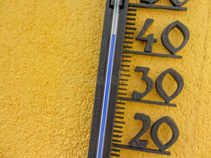 Thermomètre dans le mur jaune mesurant la température de l'air externe plus de quarante degrés Celsius images libres de droits