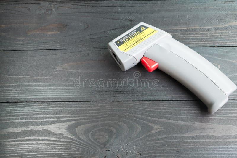 Thermomètre infrarouge sur le fond en bois photo libre de droits