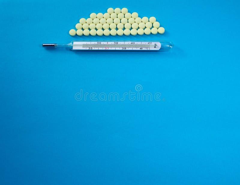Thermomètre médical traditionnel et pilules jaunes photographie stock libre de droits