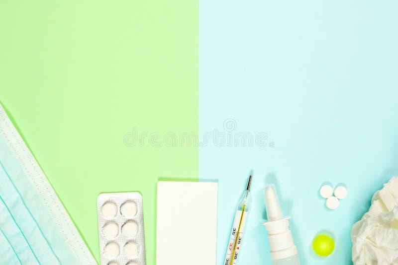 Thermomètre, mouchoirs, médecines, masque médical et pulvérisation nasale sur le fond vert-bleu Traitement de froid et de grippe photo stock
