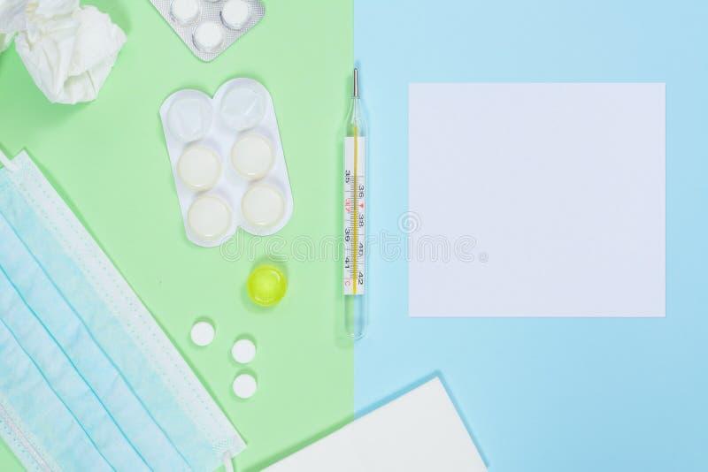 Thermomètre, mouchoirs, médecines, masque médical sur le fond vert-bleu Concept froid et de grippe de traitement avec image stock