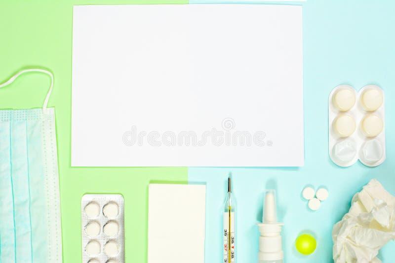 Thermomètre, mouchoirs, médecines, masque médical sur le fond vert-bleu Concept froid et de grippe de traitement avec photos stock