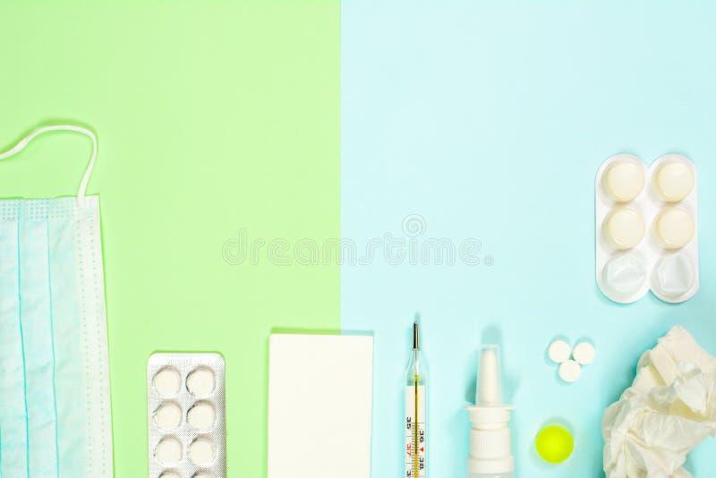 Thermomètre, mouchoirs, médecines, masque médical sur le fond vert-bleu Concept froid et de grippe de traitement avec image libre de droits
