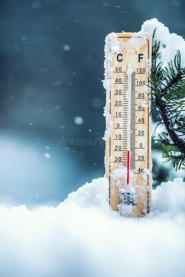 Thermometer auf Schnee zeigt niedrige Temperaturen in Celsius oder im farenheit stockfoto