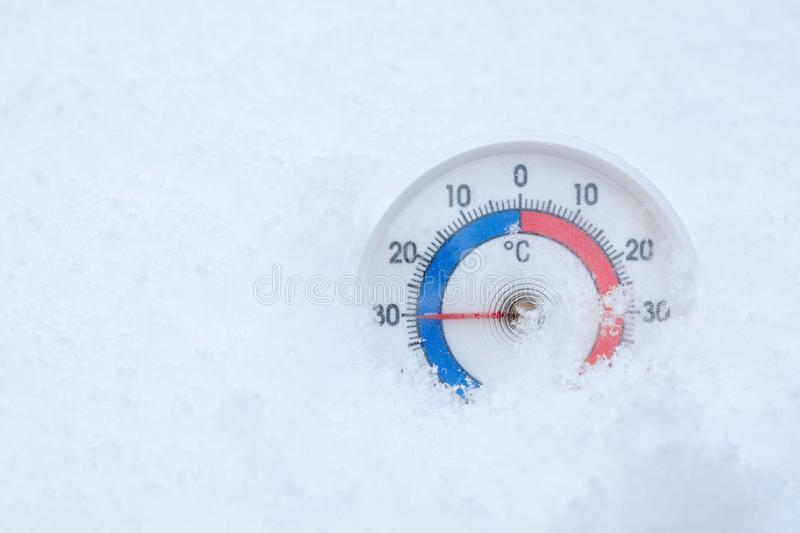 Outdoor thermometer in snow shows minus 30 Celsius degree extreme cold winter weather concept royalty free stock images