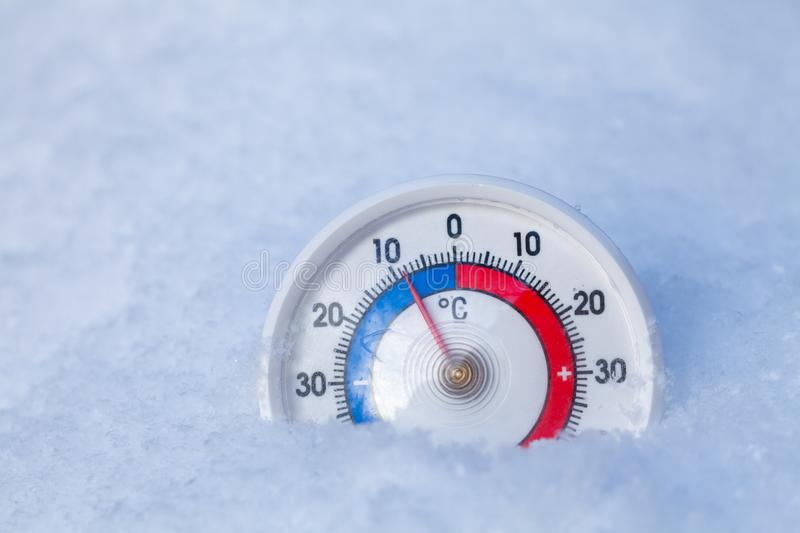 Snowed thermometer shows minus 9 Celsius degree cold winter weather concept royalty free stock photos