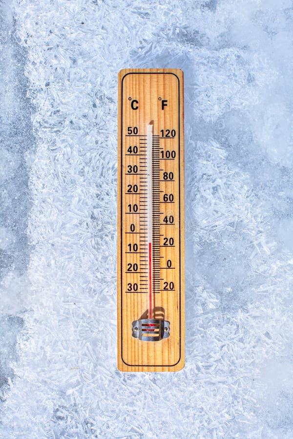 Thermometer, der auf das Eis, stellend minus 5 Grad legt dar Sun, der von der Seite scheint Winter/niedrige kommende Temperaturen lizenzfreie stockfotografie