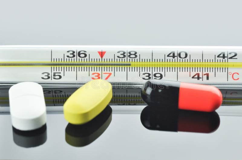 Thermometer and different pills and capsule. Mercury thermometer and different pills and capsule on a glossy black surface. Thermometer showing the temperature stock image