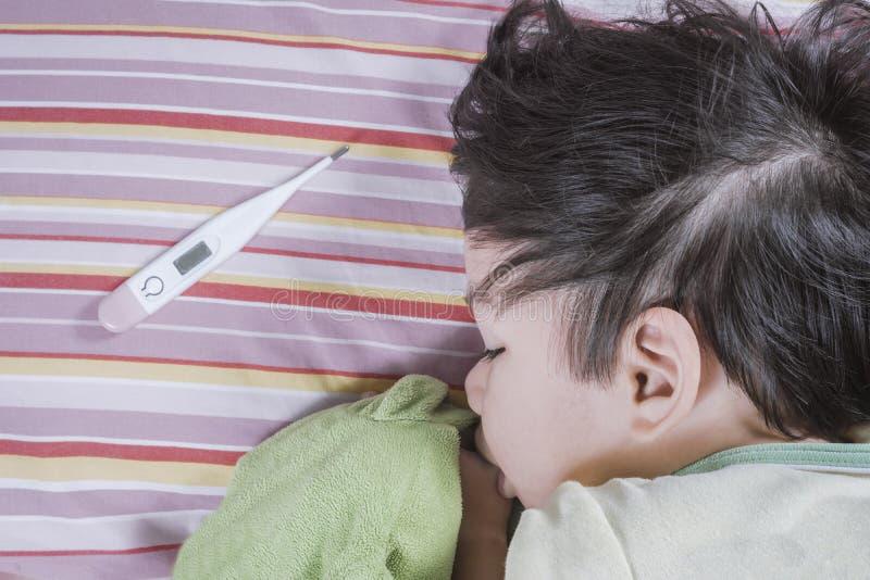 Thermometer en van Azië de zieken van de babyjongen op bed stock afbeelding