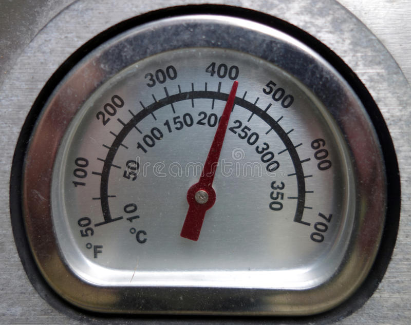 A thermometer in fahrenheit and celcius degrees. A picture of a heat gauge on a gas barbecue royalty free stock images