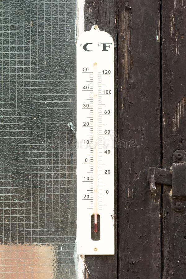 Thermometer with Fahrenheit and Celcius scales. In garden royalty free stock photography