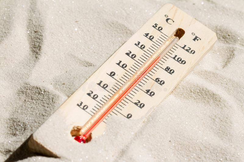 Thermometer on the hot sand global warming concept. Closeup stock photography