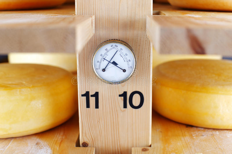 Thermometer and Hygrometer in a cheese cellar. Allowing for correct temperature and humidity during the maturation of the cheese stock image