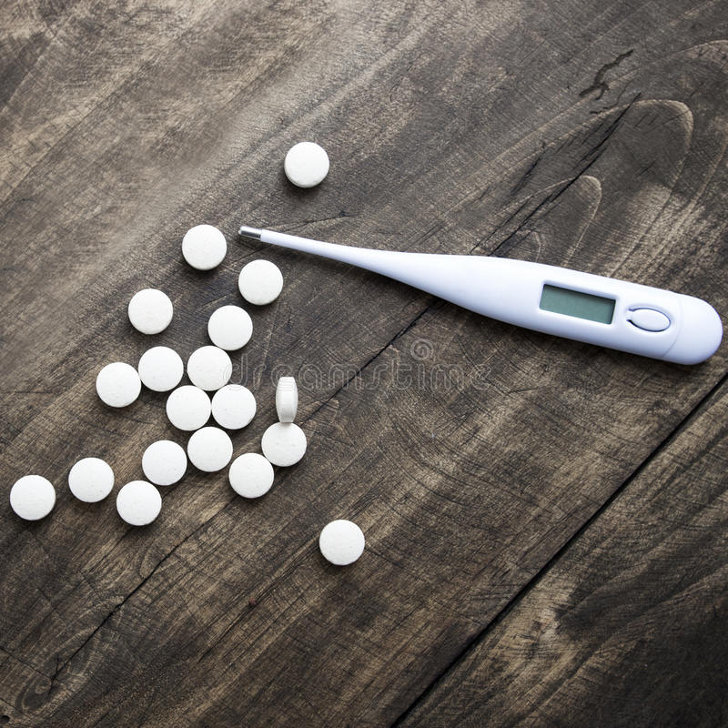 Thermometer and pills on table. stock photography