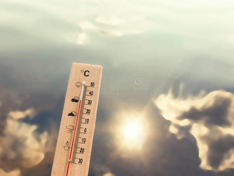 Thermometer showing 30 degrees of heat against the backdrop of lake water with the reflection of clouds and the sun.  stock images